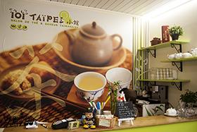 Intérieur du 101 Taïpei 小館, avec comptoir, figurine de pompier Taiwanais et décoration de type tableau au premier plan, verre dans le fond à droite et grande affiche qui représente une théiaire et des tasses de thé avec écrit 101 Taïpei 小館