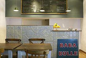 Interieur de Baba Bulle, table et chaise en premier plan, comptoire et cuisine ne second plan